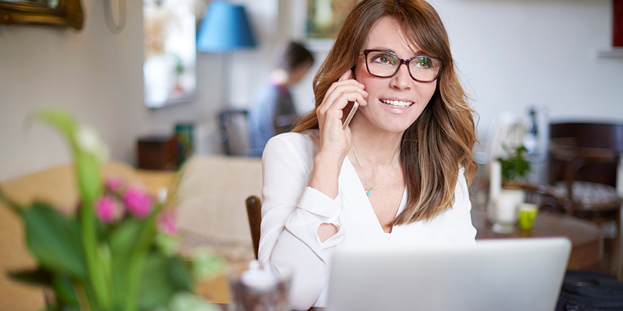 woman talking on smartphone while using laptop